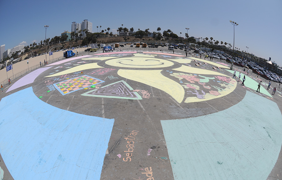 "IMAGE DISTRIBUTED FOR ROSEART - Beverley Mitchell teamed up with RoseArt to create a ""football field-sized"" chalk-paint mural at the Santa Monica Pier on Tuesday, May 19, 2015 in Santa Monica, Calif.  Designed to celebrate art and creativity now that the weather is getting warmer from coast-to-coast, the 40,000 square foot mural featured a giant sun with seven interactive play zones for kids and beachgoers to enjoy.  To support this effort nationally, RoseArt donated $50,000 to Boys & Girls Clubs of America during the event to support Clubs art programs.  (Carlos Delgado/ AP Images for RoseArt)"