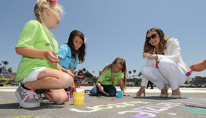 """IMAGE DISTRIBUTED FOR ROSEART - Beverley Mitchell teamed up with RoseArt to create a """"football field-sized"""" chalk-paint mural at the Santa Monica Pier on Tuesday, May 19, 2015 in Santa Monica, Calif.Designed to celebrate art and creativity now that the weather is getting warmer from coast-to-coast, the 40,000 square foot mural featured a giant sun with seven interactive play zones for kids and beachgoers to enjoy.To support this effort nationally, RoseArt donated $50,000 to Boys & Girls Clubs of America during the event to support Clubs art programs.(Carlos Delgado/ AP Images for RoseArt)"""